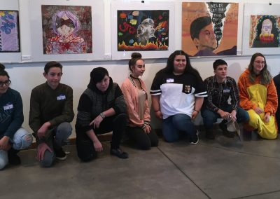 Students kneeling in a row in front of their paintings