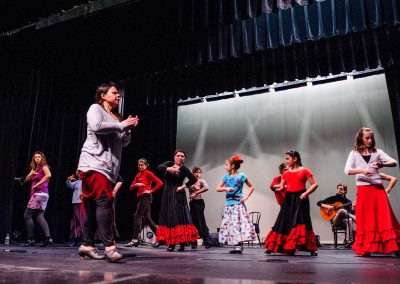 Woman instructing girls in flamenco dancing onstage with classical guitar player in the background