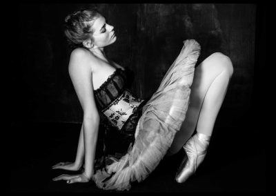 Black and white photo of ballerina in a S curved pose with hands and feet touching the floor
