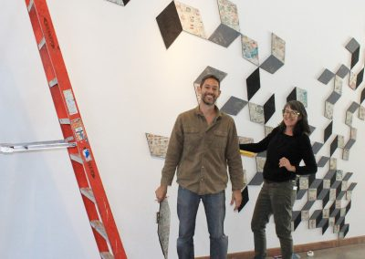 Two people standing in front of an abstract at installation with a ladder to the left
