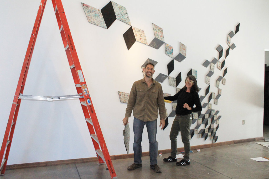 Two people standing in front of an abstract art installation