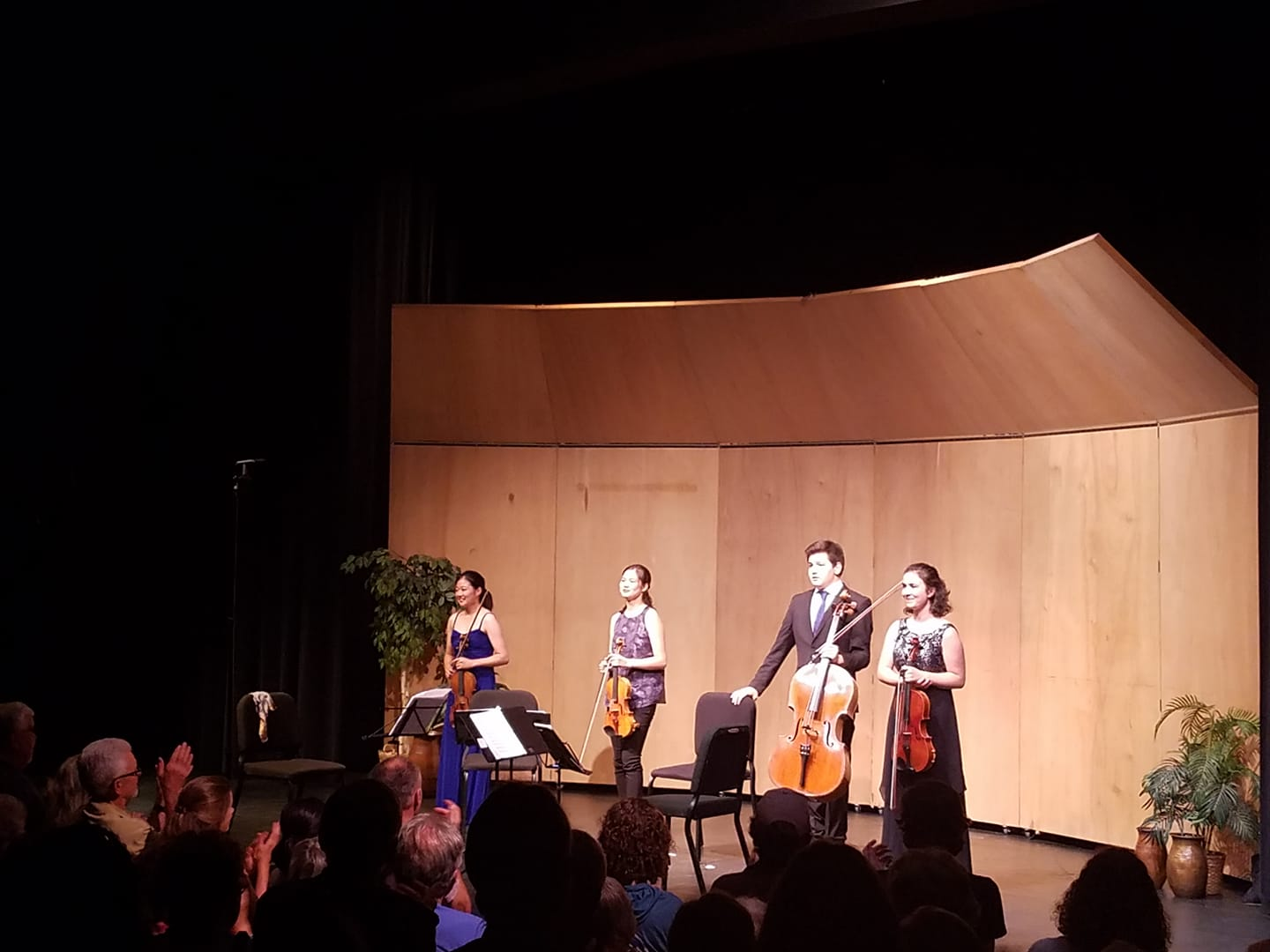 Student quartet with three violins and a cello standing onstage