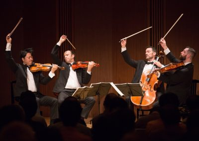 A quartet comprised of three violins and a cello performing onstage